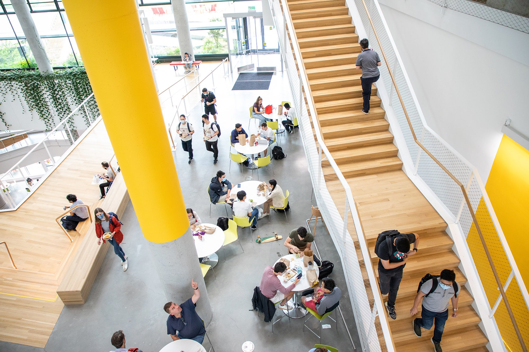 Students sit at tables and walk up stairs in a bright new building with a yellow column