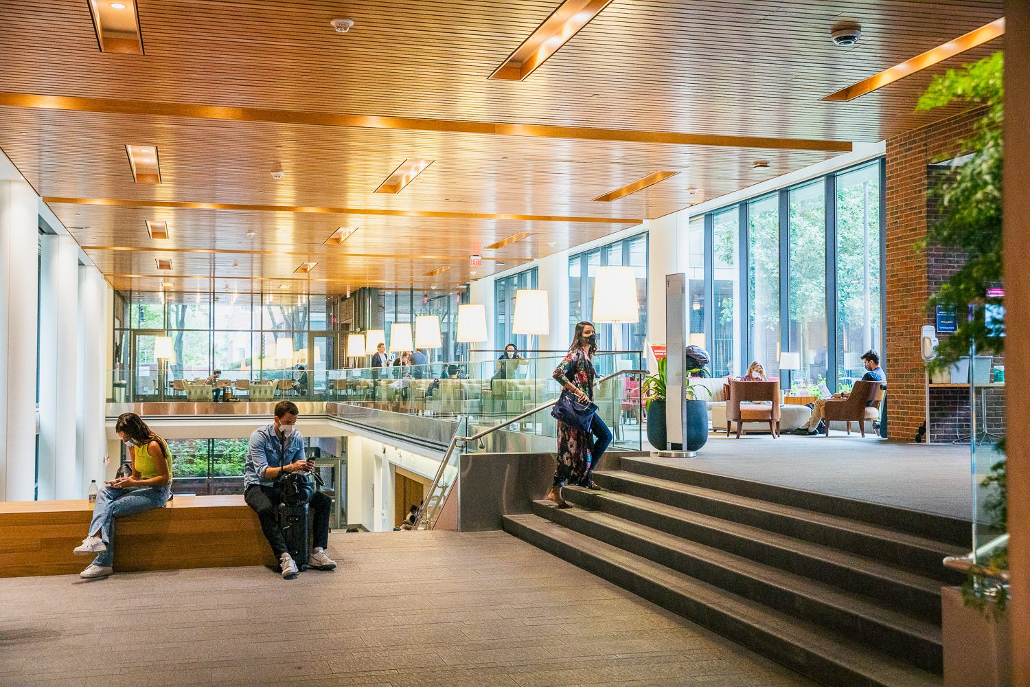 Students wearing masks sit in an open sunny space