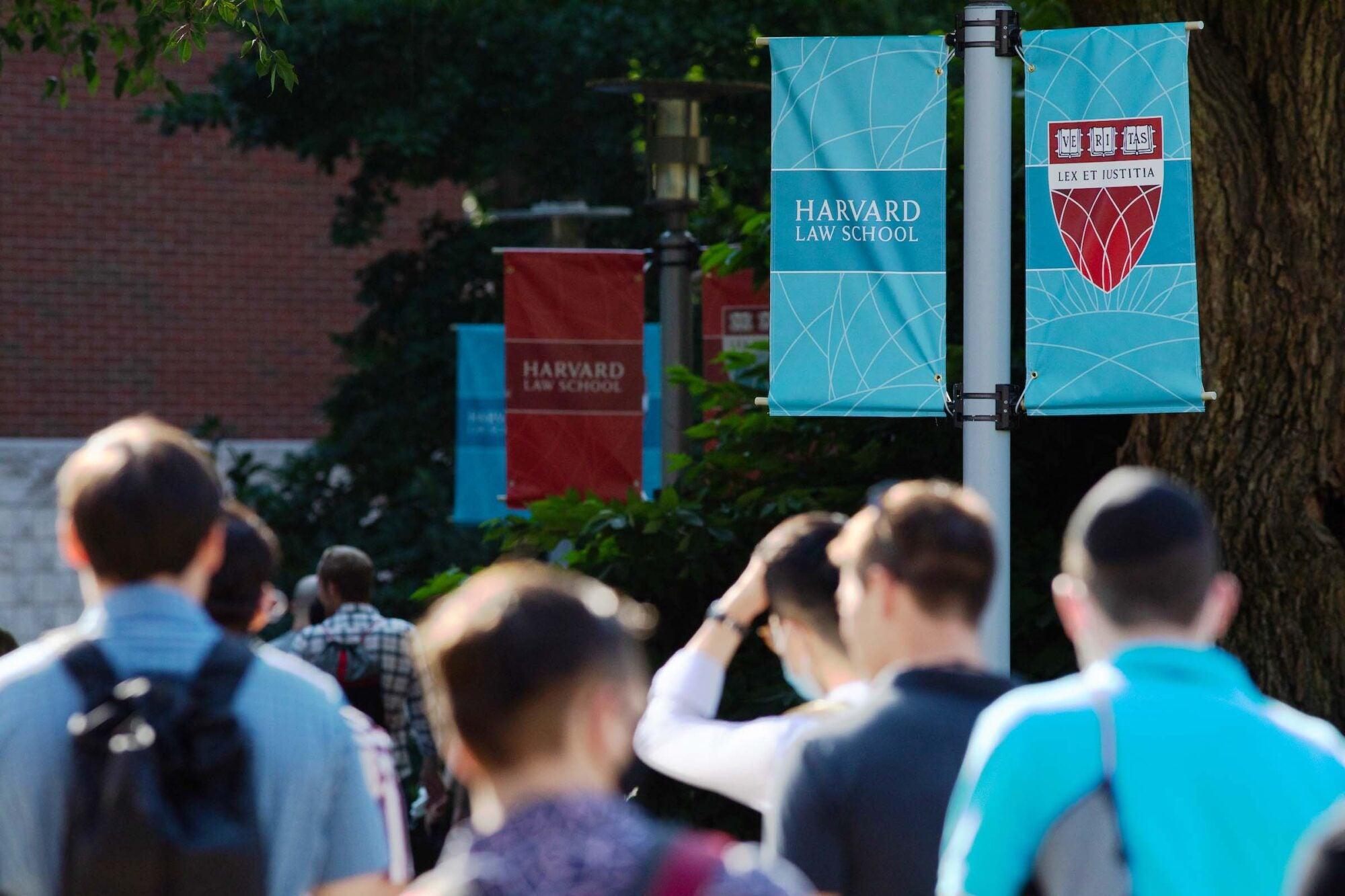 Students walk below Harvard Law School banners