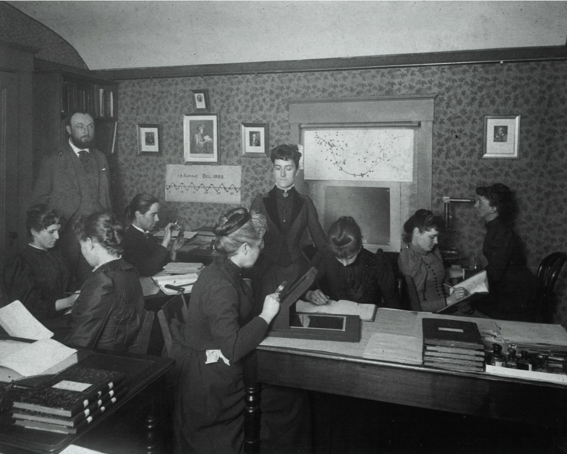 image of women working at a desk in turn of century clothing.