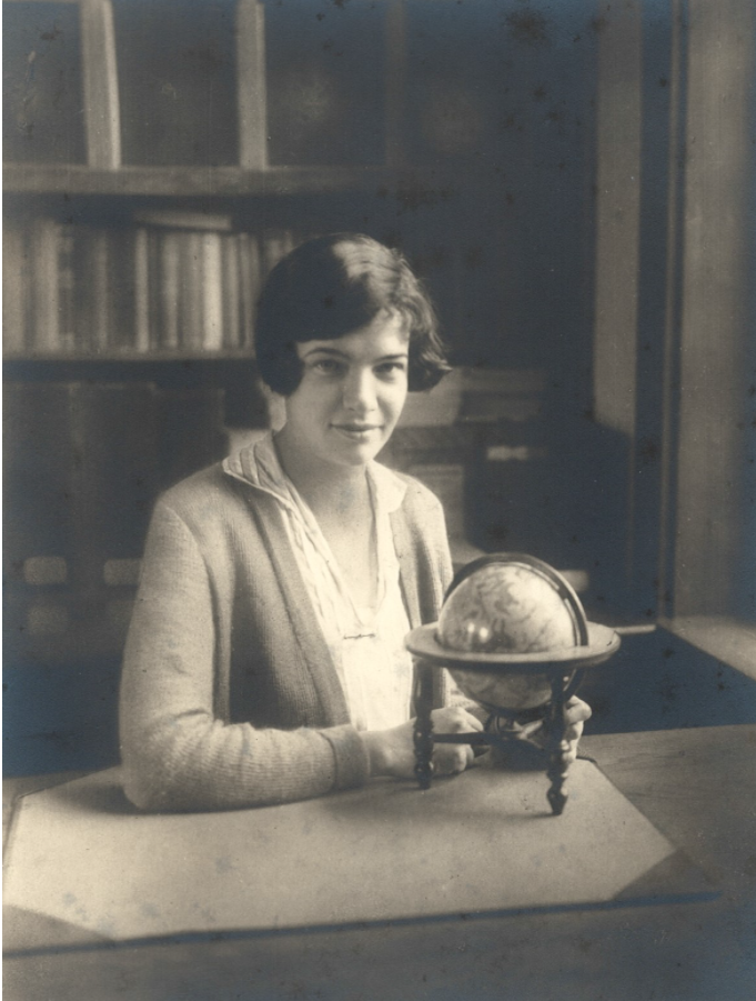 black and white photo seated at a desk behind a globe.
