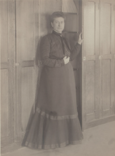 old image of woman standing by a bookshelf in turn of century dress.
